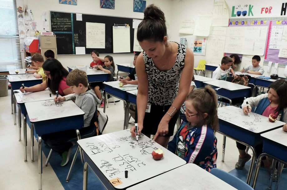 Second-grade Math Teacher Savanna Bartolo helps Caydence Huffman with a math problem in class, May 10, 2018. Texas's low-ranking public schools are primarily in poor neighborhoods — what can be done to make all schools good schools? Photo: Kin Man Hui /San Antonio Express-News / ©2018 San Antonio Express-News