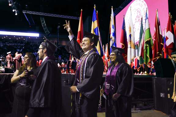 A Texas A&M International University graduate waves to the crowd during the TAMIU Commencement Ceremony on Friday, May 18 at the Laredo Energy Arena in Laredo, Texas.
