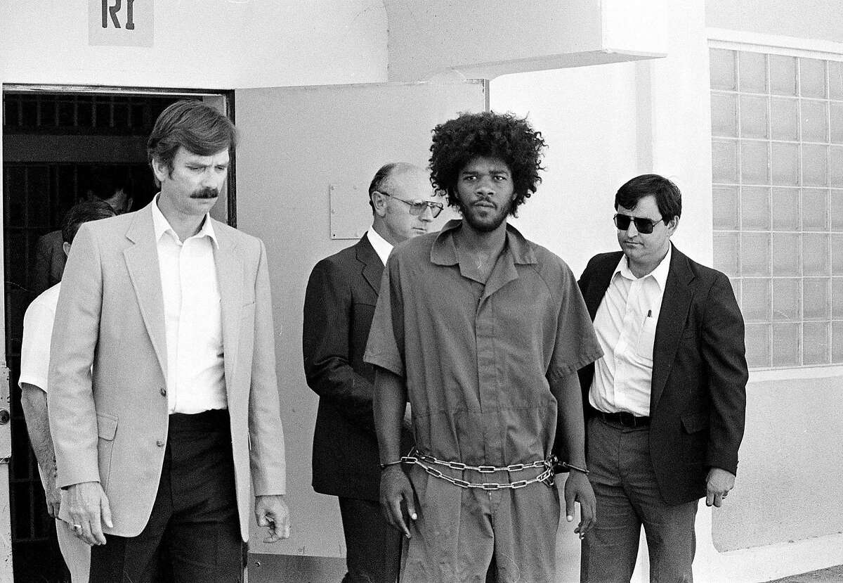 In this July 31, 1983 photo, Kevin Cooper, center, a suspect in connection with the slashing death of four people in Chino, is escorted to a car for transport to San Bernadino from Santa Barbara after he was arrested by police.