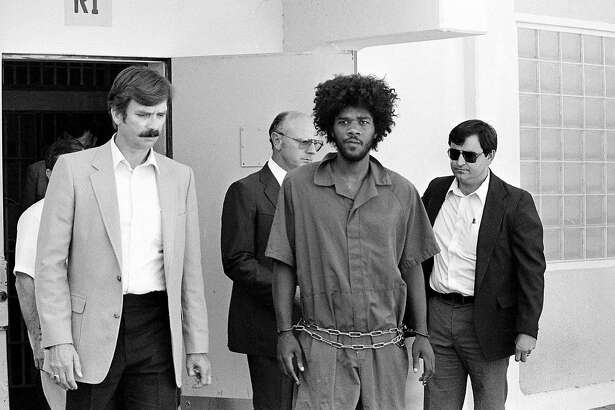 FILE - In this July 31, 1983, file photo, Kevin Cooper, center, a suspect in connection with the slashing death of four people in Chino, is escorted to a car for transport to San Bernadino from Santa Barbara, Calif., after he was arrested by police at Santa Cruz Island. U.S. Sen. Kamala Harris says California's governor should allow advanced DNA testing that advocates say could exonerate a death row inmate, Friday, May 18, 2018. The 60-year-old inmate was convicted of the 1983 Los Angeles-area hatchet and knife killings of four people. Kevin Cooper's clemency request is being reviewed by Gov. Jerry Brown's office. Two previous DNA tests concluded Cooper was the killer. California hasn't executed anyone since 2006. (AP Photo/File)