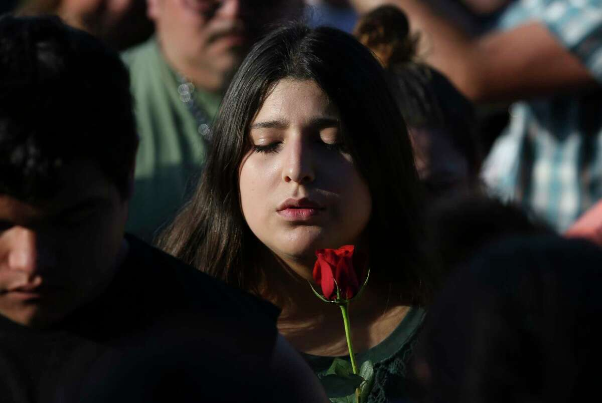 A girl closes her eyes and says prayer during a candlelight vigil for victims and survivors of the Santa Fe High School shooting at Texas First Bank on Friday, May 18, 2018, in Santa Fe. Hundreds participated and Gov. Greg Abbott and U.S. Sen. Ted Cruz also spoke at the vigil.
