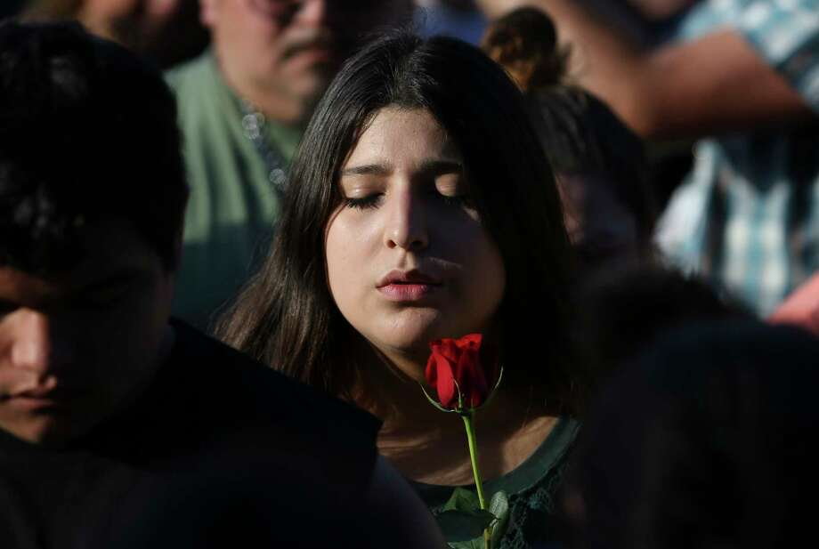 A girl closes her eyes and says prayer during a candlelight vigil for victims and survivors of the Santa Fe High School shooting at Texas First Bank on Friday, May 18, 2018, in Santa Fe. Hundreds participated and Gov. Greg Abbott and U.S. Sen. Ted Cruz also spoke at the vigil. Photo: Yi-Chin Lee, Houston Chronicle / © 2018 Houston Chronicle