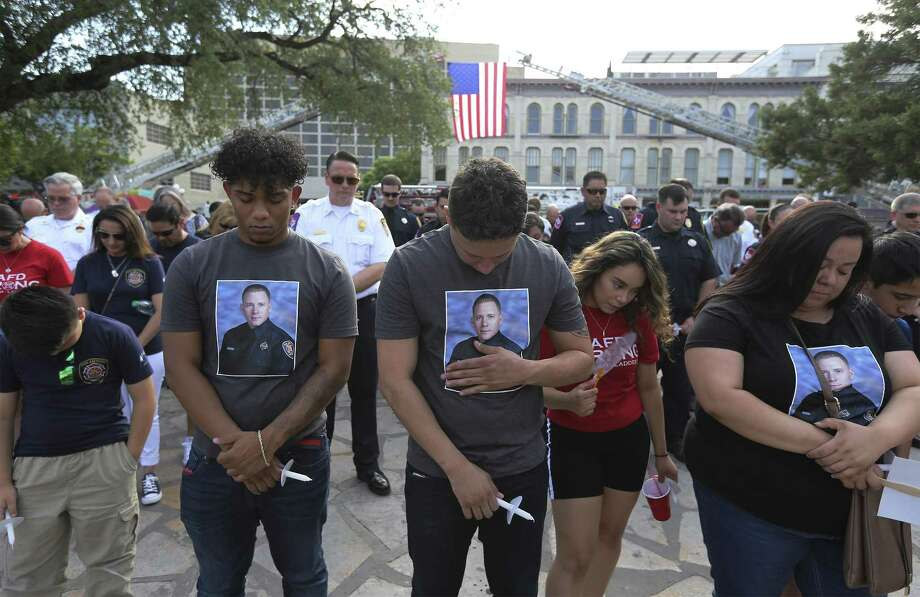 Ray Garcia (center) places his hand on an image of Scott Deem on this shirt as he joins other family members in paying tribute to the fallen firefighter on the anniversary of Deem's death on Friday, May 18, 2018. Garcia and his other family members are relatives of the firefighter. The San Antonio Fire Department in conjunction with the San Antonio Professional Firefighters Local 624 honors fallen firefighter Scott Deem on May 18, 2018 in Alamo Plaza. Deem died fighting a fire at the Ingram Square II shopping center on May 18, 2017. Fellow firefighters gathered with family and friends of Deem as a U.S. Flag lightly flapped in the breeze held on by two ladder trucks in Alamo Plaza. A moment of silence honored the anniversary of Deem's death as people held candles that wouldn't stay lit in the breeze. An artist unveiled artwork on the side of Station 35's newest truck with a likeness of Deem so that his sacrifice to service may never be forgotten. (Kin Man Hui/San Antonio Express-News) Photo: Kin Man Hui, Staff / San Antonio Express-News / ©2018 San Antonio Express-News