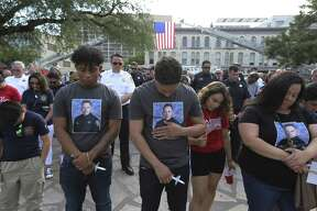 Ray Garcia (center) places his hand on an image of Scott Deem on this shirt as he joins other family members in paying tribute to the fallen firefighter on the anniversary of Deem's death on Friday, May 18, 2018. Garcia and his other family members are relatives of the firefighter. The San Antonio Fire Department in conjunction with the San Antonio Professional Firefighters Local 624 honors fallen firefighter Scott Deem on May 18, 2018 in Alamo Plaza. Deem died fighting a fire at the Ingram Square II shopping center on May 18, 2017. Fellow firefighters gathered with family and friends of Deem as a U.S. Flag lightly flapped in the breeze held on by two ladder trucks in Alamo Plaza. A moment of silence honored the anniversary of Deem's death as people held candles that wouldn't stay lit in the breeze. An artist unveiled artwork on the side of Station 35's newest truck with a likeness of Deem so that his sacrifice to service may never be forgotten. (Kin Man Hui/San Antonio Express-News)