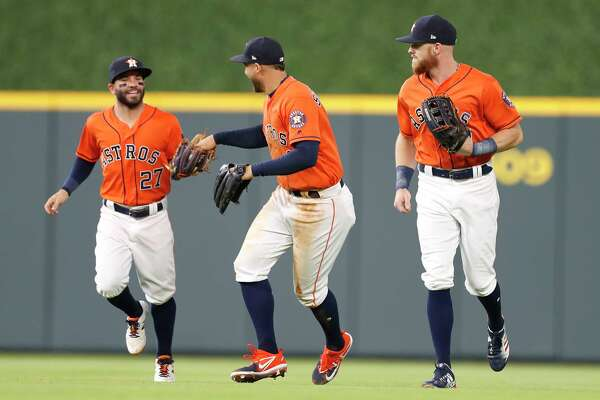 Houston Astros second baseman Jose Altuve (27) laughs with George Springer (4)  after Springer caught Cleveland Indians Yan Gomes' flyout during the second inning of an MLB baseball game at Minute Maid Park, Friday, May 18, 2018, in Houston.