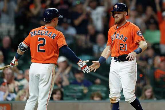 Houston Astros left fielder Derek Fisher (21) celebrates with Alex Bregman (2) after scoring a run during the seventh inning of an MLB baseball game at Minute Maid Park, Friday, May 18, 2018, in Houston.