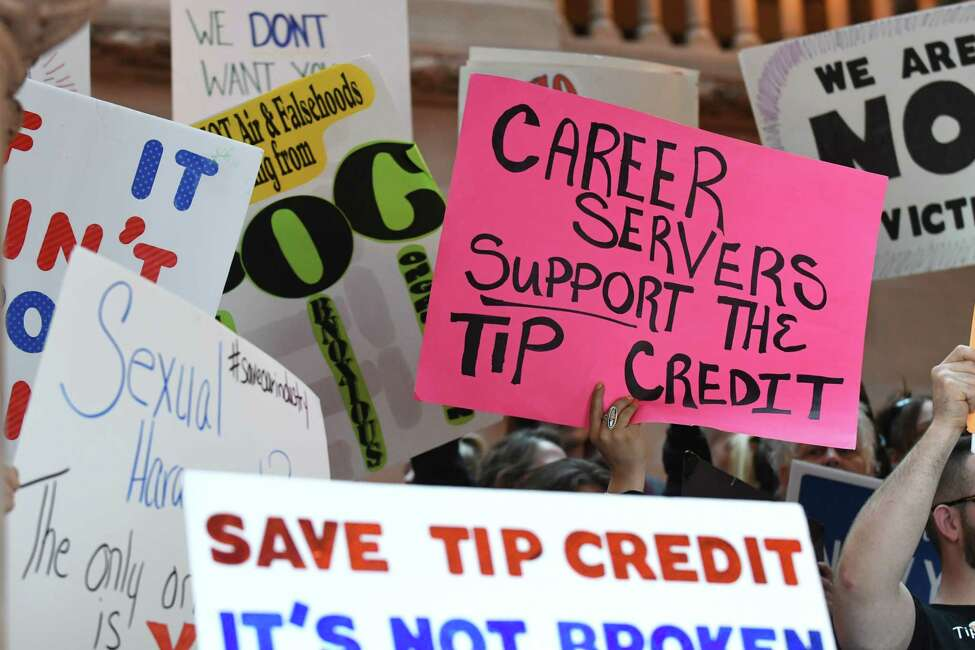 Restaurant workers hold signs during a press conference to demonstrate against a proposed plan to eliminate the stateOs tip credit on Friday, May 18, 2018, in Albany, N.Y. Tip credit is the amount between what a tipped employee makes and what the established minimum wage is. Gov. Andrew Cuomo directed the Commissioner of Labor to set up public hearings to look at the possibility of eliminating minimum wage tip credits across the state. (Will Waldron/Times Union)