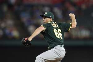 Oakland Athletics relief pitcher Ryan Dull (66) throws to the Texas Rangers in the eighth inning of a baseball game Tuesday, April 24, 2018, in Arlington, Texas. (AP Photo/Richard W. Rodriguez)
