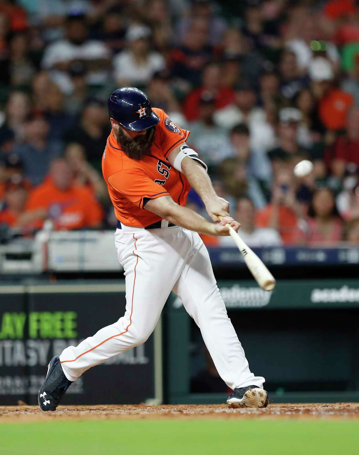 Houston Astros Evan Gattis (11) hits a sacrifice fly to score Carlos Correa during the eighth inning of an MLB baseball game at Minute Maid Park, Friday, May 18, 2018, in Houston.