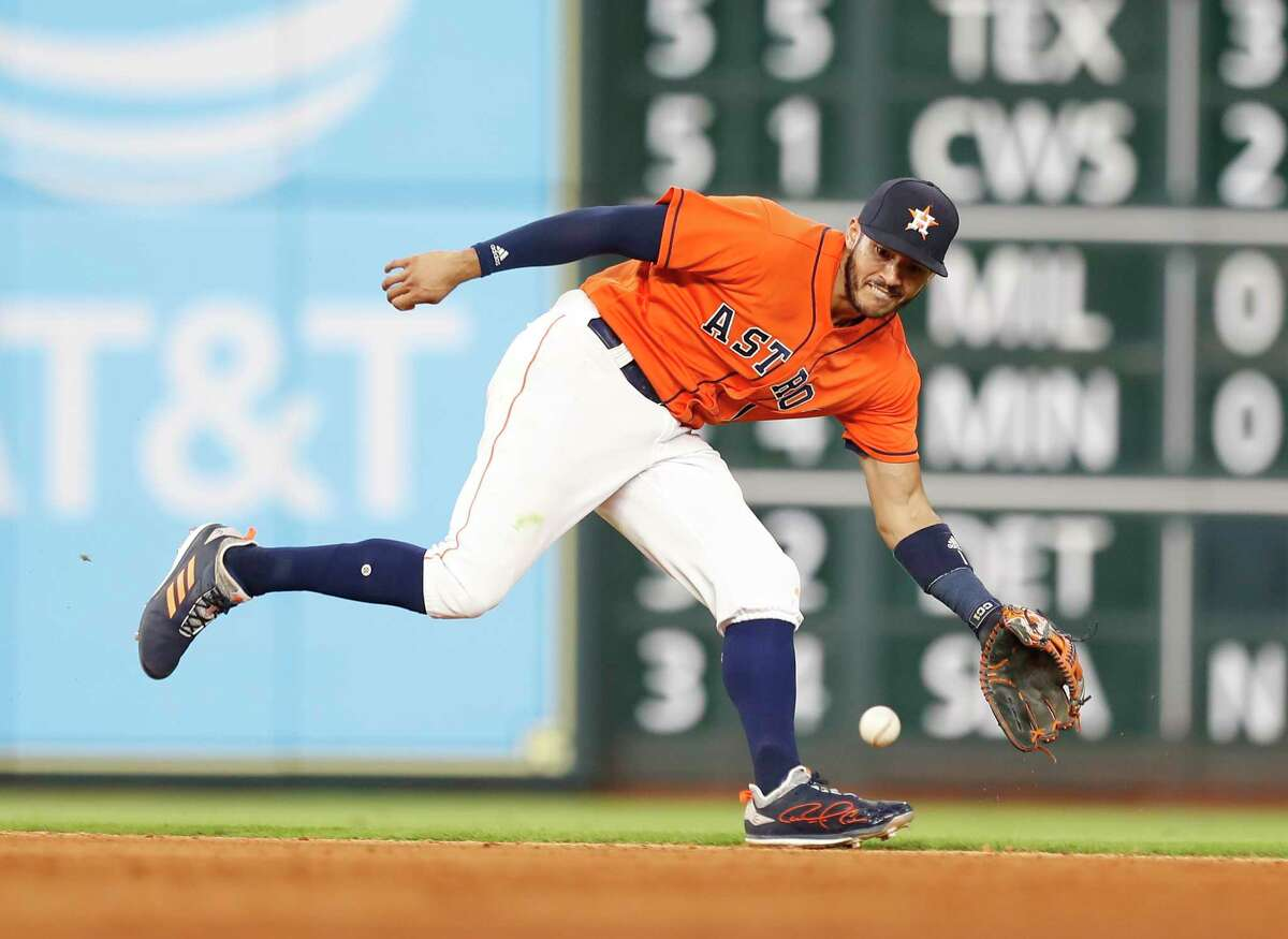 Houston Astros shortstop Carlos Correa (1) reaches for Cleveland Indians catcher Yan Gomes' single during the ninth inning of an MLB baseball game at Minute Maid Park, Friday, May 18, 2018, in Houston.