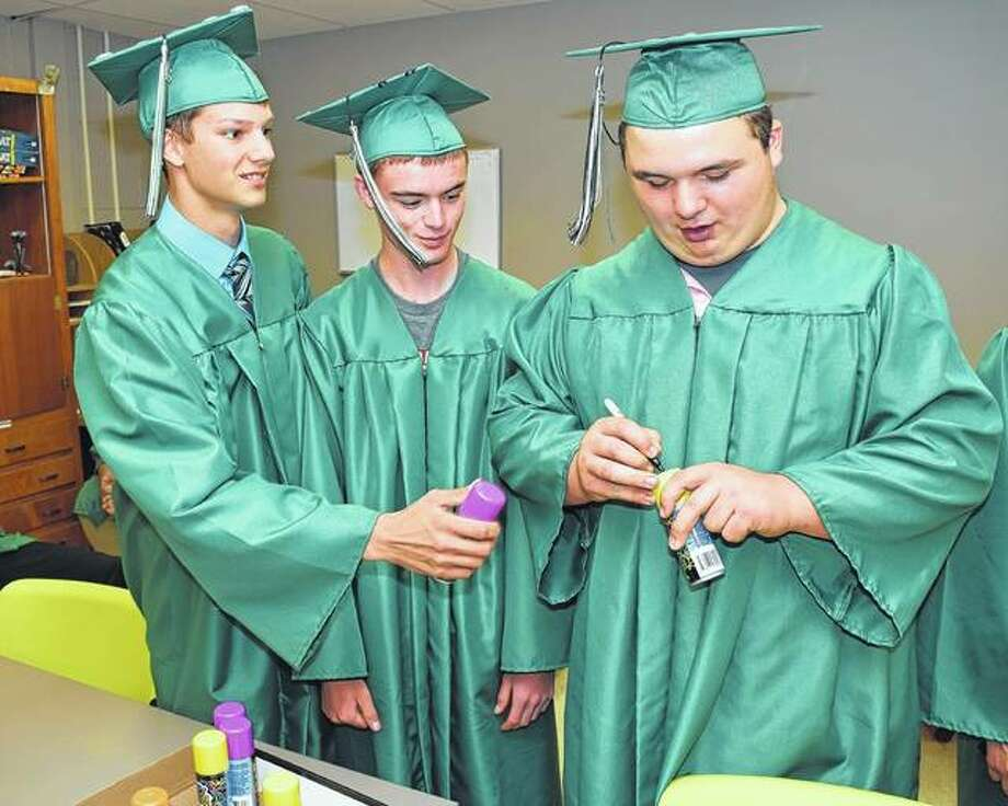 Three Carrollton High School seniors sign their cans of Silly String prior to Friday night's graduation. Photo:     David Blanchette | Journal-Courier