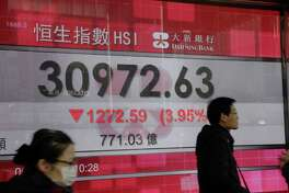 Pedestrians walk past an electronic screen displaying the Hang Seng Index figure in Hong Kong, on Feb. 6, 2018.