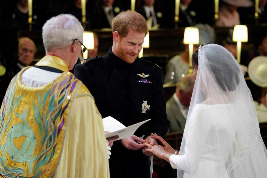 Britain's Prince Harry places the ring on Meghan Markle during their wedding ceremony at St. George's Chapel in Windsor Castle in Windsor, near London, England, Saturday, May 19, 2018. (Jonathan Brady/pool photo via AP) Photo: Jonathan Brady, AP / WPA Rota