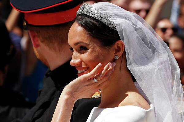 Meghan Markle reacts as she rides in a carriage with her husband Britain's Prince Harry after their wedding ceremony at St. George's Chapel in Windsor Castle in Windsor, near London, England, Saturday, May 19, 2018. (John Sibley/pool photo via AP)