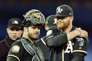 Oakland Athletics starting pitcher Brett Anderson, right, holds his arm as catcher Josh Phegley looks on in the second inning of a baseball game against the Toronto Blue Jays in Toronto, Friday, May 18, 2018. (Frank Gunn/The Canadian Press via AP)
