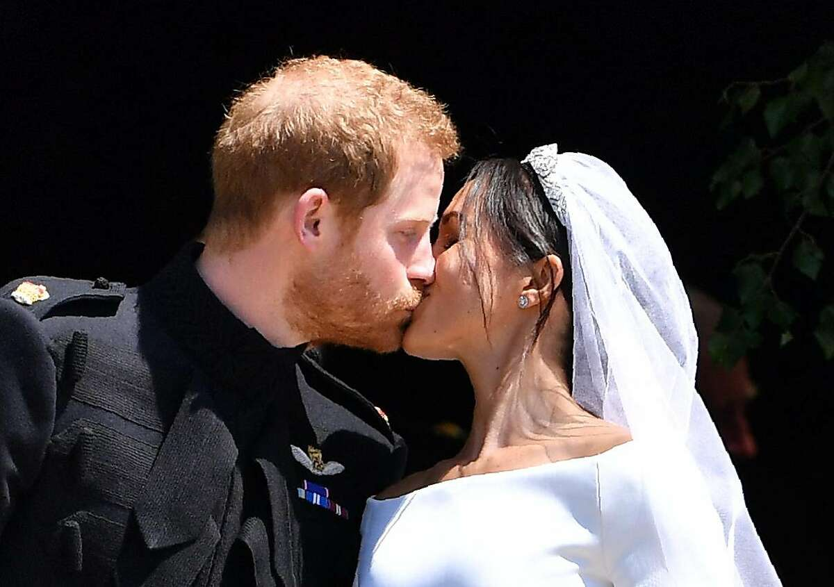Britain's Prince Harry, Duke of Sussex kisses his wife Meghan, Duchess of Sussex as they leave from the West Door of St George's Chapel, Windsor Castle, in Windsor, on May 19, 2018 after their wedding ceremony.