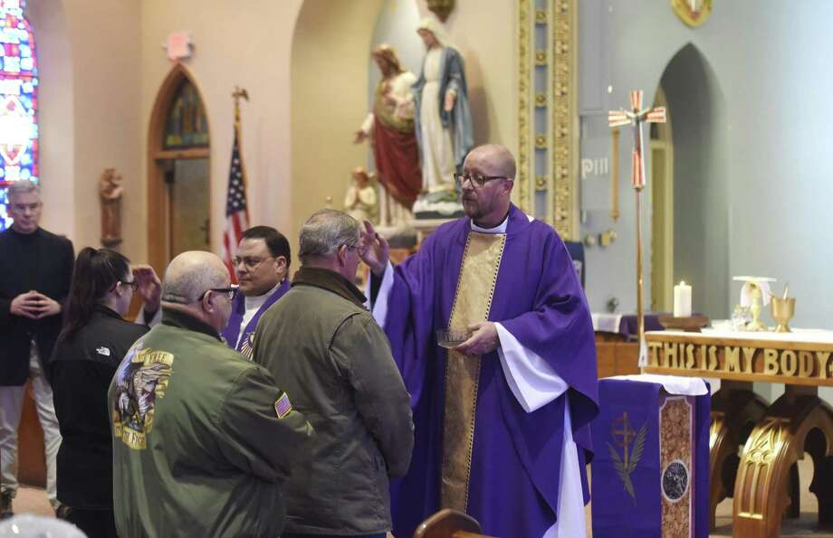 Father Arthur Mollenhauer performs his duties at the Ash Wednesday service at St. Roch's Church in the Chickahominy section of Greenwich on Feb. 14. Photo: Tyler Sizemore / Hearst Connecticut Media / Greenwich Time