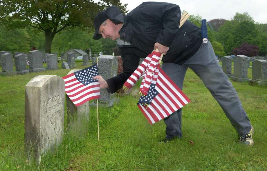 Stamford resident Hugh Jackson plants flags at the graves of veterans as the tradition that started 28 years ago, The Flag Placement Ceremony, continued on Saturday, May 19th, 2018 at St. John's Cemetery in Norwalk, Conn. For the past 5 years King has been the proud sponsor of the  here in Norwalk. The event takes place once a year near Memorial Day, where volunteers place flags on the graves of more than 5,000 military veterans across eight Norwalk Cemeteries. Photo: Erik Trautmann / Hearst Connecticut Media / Norwalk Hour