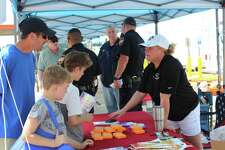 Shawn DeCandia and his sons stop at the Montgomery County 9-1-1 Emergency Communication District booth during the 2018 East 1488 Emergency Preparedness Fair on Saturday, May 19, 2018.