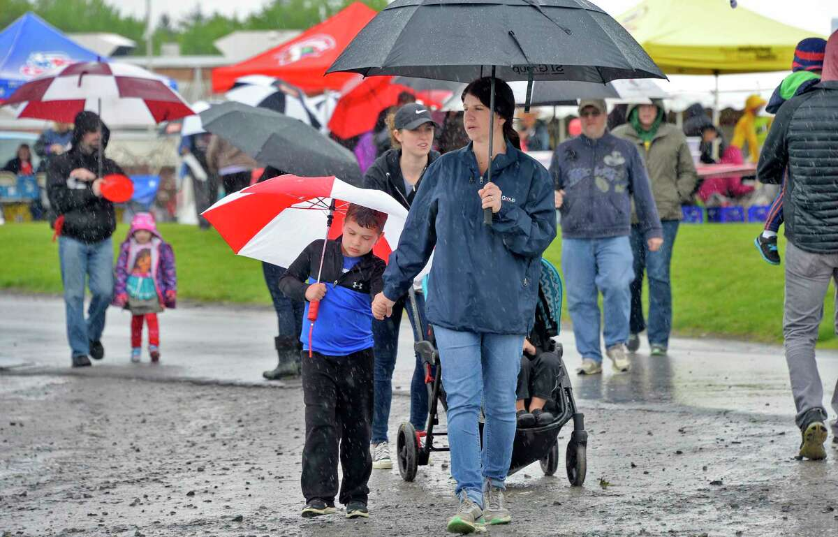 Rebecca Gleason, center, of Niskayuna and her son Nicholas, 5, join other umbrella-covered attendees at the 37th year Niska-Day Saturday May 19, 2018 in Niskayuna, NY. (John Carl D'Annibale/Times Union)