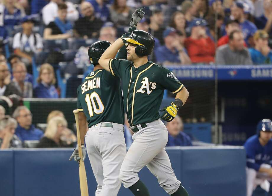 TORONTO, ON - MAY 19: Chad Pinder #18 of the Oakland Athletics is congratulated by Marcus Semien #10 after hitting a grand slam home run in the eighth inning during MLB game action against the Toronto Blue Jays at Rogers Centre on May 19, 2018 in Toronto, Canada. (Photo by Tom Szczerbowski/Getty Images) Photo: Tom Szczerbowski / Getty Images