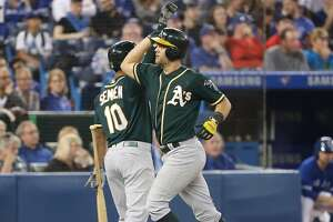 TORONTO, ON - MAY 19: Chad Pinder #18 of the Oakland Athletics is congratulated by Marcus Semien #10 after hitting a grand slam home run in the eighth inning during MLB game action against the Toronto Blue Jays at Rogers Centre on May 19, 2018 in Toronto, Canada. (Photo by Tom Szczerbowski/Getty Images)