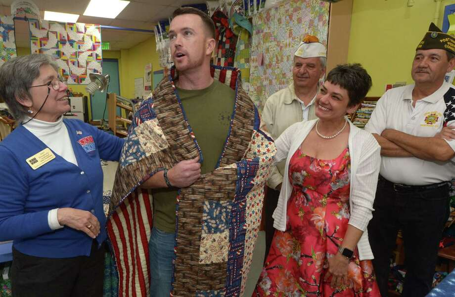 Quilts of Valor Foundation Connecticut State Coordinator, Jane Dougherty, left and Christy Ruiz owner of Christy's Quilting Boutique present Quilts of Valor to veterans including Marine Corps veteran Mark Blinn as Army Veteran John Deilus and Navy veteran Bernie Rombout look on during a nationwide program at Christy's Quilting Boutique Saturday, May 19, 2018, in Norwalk, Conn. Christy's has donated 300 or so quilts to veterans over the years. Photo: Erik Trautmann / Hearst Connecticut Media / Norwalk Hour