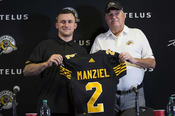 Former NFL quarterback and Heisman Trophy winner Johnny Manziel, left, holds a jersey with Hamilton Tiger-Cats head coach June Jones after announcing that he has signed a two-year contract to play for the CFL team at a press conference in Hamilton, Ontario, Saturday, May 19, 2018. (Aaron Lynett/The Canadian Press via AP)
