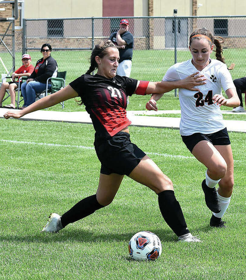Edwardsville's Rileigh Kuhns, right, goes for the ball despite a push from Granite City defender Abby Reeves during the first half of Saturday's championship game of the Granite City Class 3A Regional at Gene Baker Field. Photo:       Matt Kamp | For The Telegraph