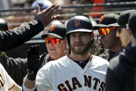 San Francisco Giants' Brandon Crawford, center, celebrates his two-run home run with teammates in the dugout during the sixth inning of a baseball game against the Colorado Rockies, Saturday, May 19, 2018, in San Francisco. (AP Photo/Marcio Jose Sanchez)