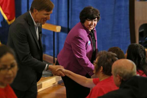 Texas Democratic Gubernatorial candidates Andrew White (left) and Lupe Valdez shake hands with audience members after their debate May 11, 2018, at St. James Episcopal Church in Austin.