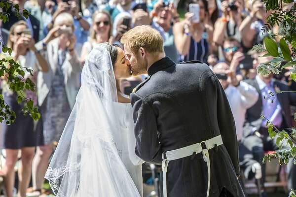 Meghan Markle and Prince Harry kiss on the steps of St George's Chapel after  their wedding ceremony in Windsor Castle in Windsor, near London, England, Saturday, May 19, 2018. (Danny Lawson/pool photo via AP)