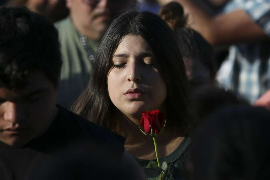 A girl closes her eyes and says prayer during a candlelight vigil for victims and survivors of the Santa Fe High School shooting at Texas First Bank on Friday, May 18, 2018, in Santa Fe. Hundreds participated and Gov. Greg Abbott and U.S. Sen. Ted Cruz also spoke at the vigil. ( Yi-Chin Lee / Houston Chronicle )