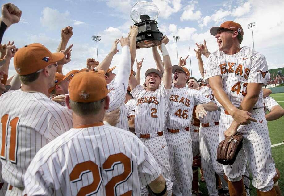 Texas' Kody Clemens (2) and Brandon Ivey (46) hoist the Big 12 regular-season championship trophy. Photo: Jay Janner / Associated Press / Austin American-Statesman