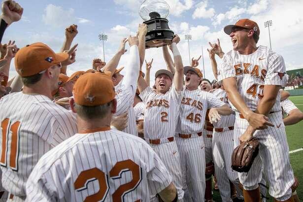 Texas' Kody Clemens (2) and Brandon Ivey (46) hoist the Big 12 regular-season championship trophy.