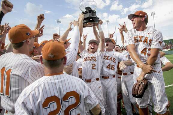 Texas' Kody Clemens (2) and Brandon Ivey (46) hoist the Big 12 regular-season championship trophy.