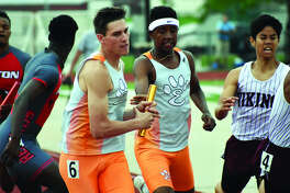 Edwardsville's Ben Ryan, left, takes the baton from Brandon Battle to run the last leg of the 1,600-meter relay during the Class 3A Belleville West Sectional on Saturday in Belleville.