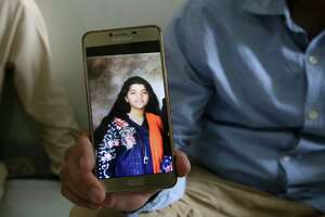 Abdul Aziz Sheikh, center, father of Sabika Sheikh, a victim of a shooting at a Texas high school, shows a picture of his daughter in Karachi, Pakistan, Saturday, May 19, 2018.  The Pakistani foreign exchange student is among those killed in the shooting, according to a leader at a program for foreign exchange students and the Pakistani Embassy in Washington, D.C. Megan Lysaght, manager of the Kennedy-Lugar Youth Exchange & Study Abroad program (YES), sent a letter to students in the program confirming that Sabika Sheikh was killed in the shooting. (AP Photo/Fareed Khan)
