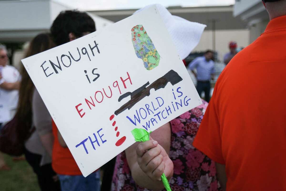 A sign is pictured during a vigil for the victims of the Santa Fe High School shooting on Saturday, May 19, 2018, at the intersection of Interstate-45 and Sawdust Road in Spring.