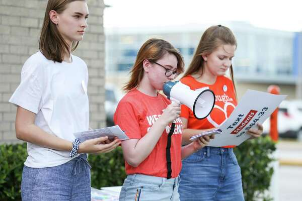 From the left, Olivia Novak, Annika Gallaway and Rebecca Fox, all of Students Demand Action, speak during a vigil for the victims of the Santa Fe High School shooting on Saturday, May 19, 2018, at the intersection of Interstate-45 and Sawdust Road in Spring.
