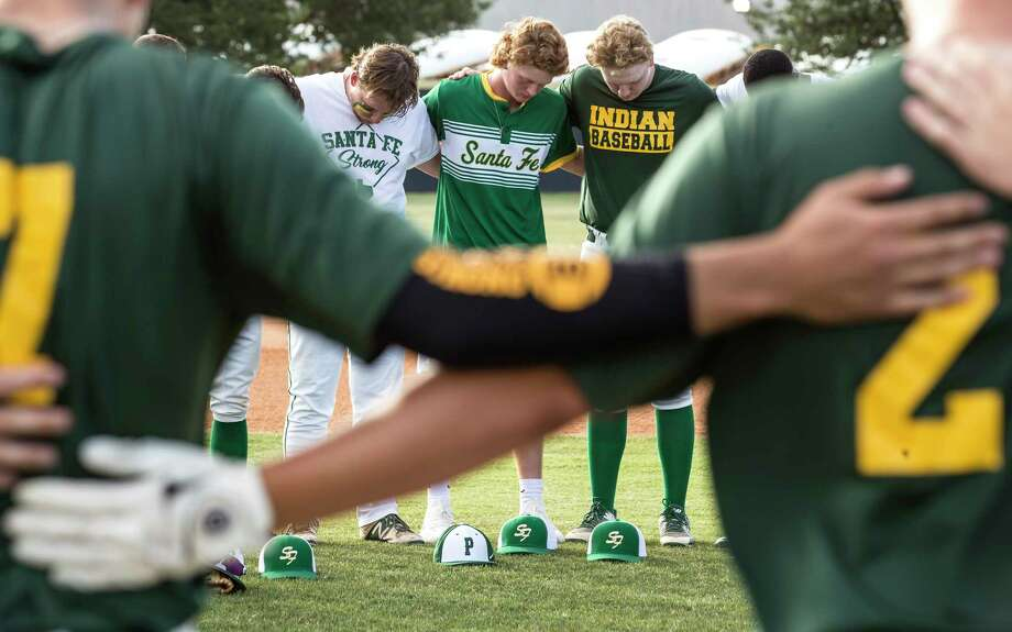 Santa Fe High School baseball player Rome Shubert, center, bows his head in prayer as he gathers with his teammates and members of the Kingwood Park baseball team before a Class 5A Region III playoff baseball game on Saturday, May 19, 2018, in Deer Park. Photo: Brett Coomer, Houston Chronicle / © 2018 Houston Chronicle
