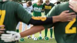 Santa Fe High School baseball player Rome Shubert, center, bows his head in prayer as he gathers with his teammates and members of the Kingwood Park baseball team before a Class 5A Region III playoff baseball game on Saturday, May 19, 2018, in Deer Park.