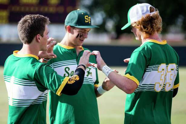 Santa Fe High School baseball players Landon Thompson (4), Trenton Beazley, center, and Rome Shubert (33) gather on the field before a Class 5A Region III playoff baseball game against Kingwood Park on Saturday, May 19, 2018, in Deer Park.