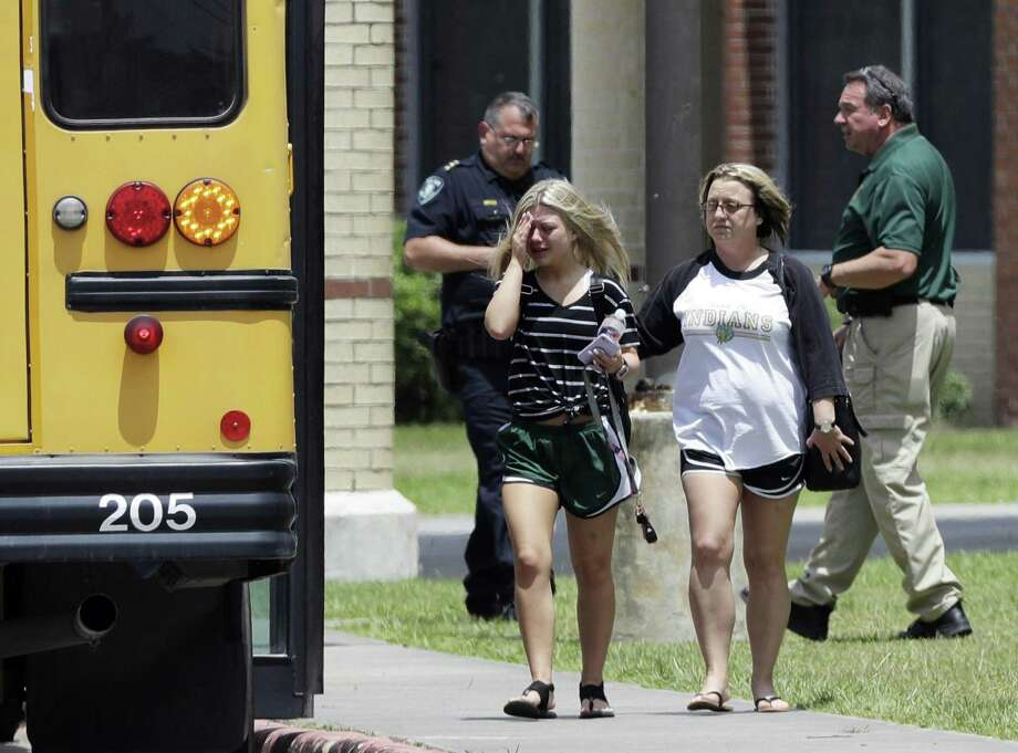 A student, left, reacts after retrieving her belongings inside Santa Fe High School in Santa Fe, Texas, on Saturday, May 19, 2018. Students and teachers were allowed to return to parts of the school to gather their belongings. A gunman opened fire inside the school Friday, May 18  killing several people. (AP Photo/David J. Phillip) Photo: David J. Phillip, STF / Associated Press / Copyright 2018 The Associated Press. All rights reserved.