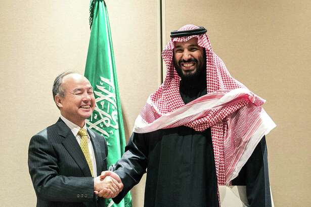 Masayoshi Son, chairman and chief executive officer of SoftBank Group (left) shakes hands with Saudi Crown Prince Mohammed bin Salman in New York, U.S., on March 27, 2018.
