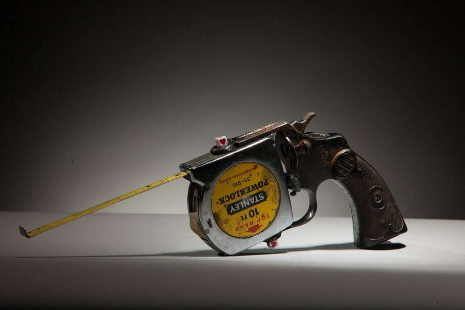 """Above, Luis Cruz Azaceta's """"Taperuler Gun,"""" 2014, a tape ruler and decommissioned handgun, courtesy of Arthur Roger Gallery, New Orleans. It is included in a new exhibition at the Fairfield University Art Museum.  Photo: Neil Alexander / Contributed Photo"""