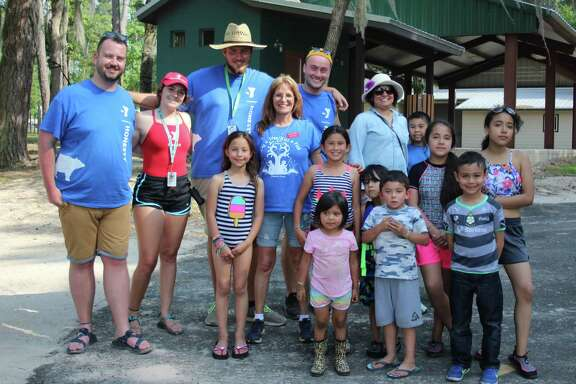 The ninth annual Hug-a-Tree/Kiss-a-Fish event hosted by the Community and Children's Impact Center was held May 18-20 at the YMCA's Camp Cullen in Trinity. Families were greeted not only by Impact Center staff such as Brenda Myers (fourth from left) but also by members of the YMCA such as Craig Gillen (left), Alyssa Stephens (second from left), Jayce Park (third from left) and Shea Murray (fifth from left).