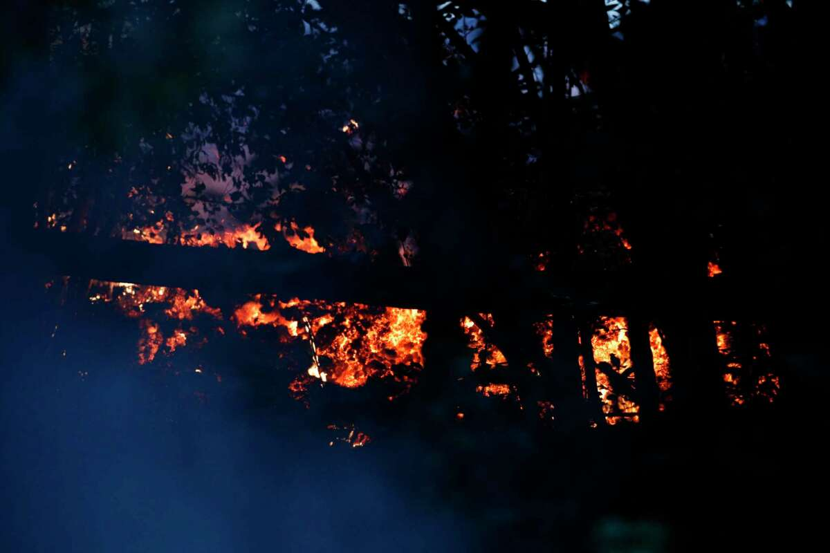 Lava burns trees as it flows toward the ocean near Pahoa, Hawaii Saturday, May 19, 2018. Two fissures that opened up in a rural Hawaii community have merged to produce faster and more fluid lava. Scientists say the characteristics of lava oozing from fissures in the ground has changed significantly as new magma mixes with decades-old stored lava.