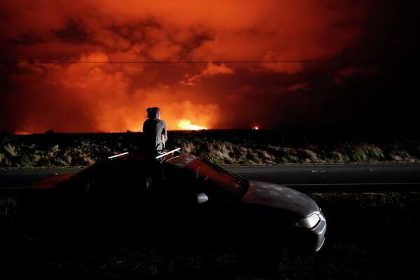 Brittany Kimball watches as lava erupts from from a fissure near Pahoa, Hawaii, Saturday, May 19, 2018. Two fissures that opened up in a rural Hawaii community have merged to produce faster and more fluid lava. Scientists say the characteristics of lava oozing from fissures in the ground has changed significantly as new magma mixes with decades-old stored lava.