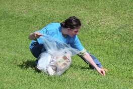Jozette Lopez picks up trash in the ditches outside of Hartz Chicken on May 19 for Clean Up Cleveland.